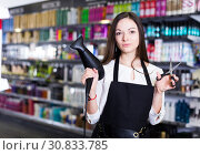 Купить «Woman hairstylist holding blow dryer and hair cutters in cosmetics salon», фото № 30833785, снято 31 марта 2018 г. (c) Яков Филимонов / Фотобанк Лори