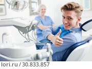 Купить «Male is sitting satisfied in chair after treatment in dental office», фото № 30833857, снято 30 апреля 2019 г. (c) Яков Филимонов / Фотобанк Лори