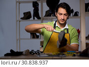 Young shoemaker in workshop at night. Стоковое фото, фотограф Elnur / Фотобанк Лори