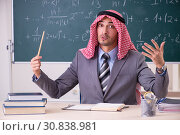 Купить «Arab teacher wearing suit in front of chalkboard», фото № 30838981, снято 21 ноября 2018 г. (c) Elnur / Фотобанк Лори