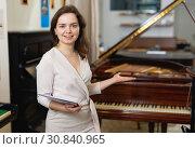 Купить «Pretty saleswoman in piano record store», фото № 30840965, снято 16 апреля 2019 г. (c) Яков Филимонов / Фотобанк Лори