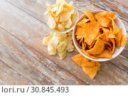 Купить «close up of potato crisps and nachos in bowls», фото № 30845493, снято 22 мая 2015 г. (c) Syda Productions / Фотобанк Лори