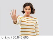 Купить «young woman making stopping gesture», фото № 30845605, снято 6 марта 2019 г. (c) Syda Productions / Фотобанк Лори