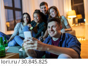 Купить «friends with smartphone and drinks at night home», фото № 30845825, снято 22 декабря 2018 г. (c) Syda Productions / Фотобанк Лори