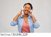 Купить «african woman in headphones listening to music», фото № 30846229, снято 2 марта 2019 г. (c) Syda Productions / Фотобанк Лори