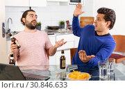 Купить «Two friends with bottles of beer celebrate happy event», фото № 30846633, снято 13 марта 2019 г. (c) Яков Филимонов / Фотобанк Лори