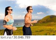 Купить «couple with phones and arm bands running on beach», фото № 30846789, снято 1 августа 2018 г. (c) Syda Productions / Фотобанк Лори