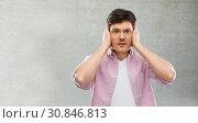Купить «man closing ears by hands over gray concrete wall», фото № 30846813, снято 3 февраля 2019 г. (c) Syda Productions / Фотобанк Лори