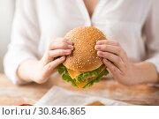 Купить «close up of woman holding hamburger», фото № 30846865, снято 21 мая 2015 г. (c) Syda Productions / Фотобанк Лори