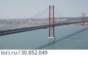 Купить «Panoramic view of 25 de Abril Bridge - suspension bridge across Tagus river connecting Lisbon city to municipality of Almada, Portugal», видеоролик № 30852049, снято 13 мая 2019 г. (c) Яков Филимонов / Фотобанк Лори