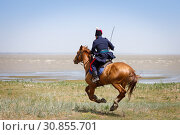 Купить «Don Cossack in blue military clothes quickly rides along the coast of the sea with a sabre in his hand», фото № 30855701, снято 18 мая 2019 г. (c) Олег Белов / Фотобанк Лори