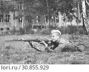 Купить «Советский солдат с винтовкой Мосина на огневой позиции приготовился к стрельбе. Старая фотография времён СССР», иллюстрация № 30855929 (c) александр афанасьев / Фотобанк Лори