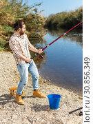 Купить «Adult man standing near river and pulling fish expressing emotions of dedication», фото № 30856349, снято 15 марта 2019 г. (c) Яков Филимонов / Фотобанк Лори