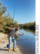 Купить «Adult man standing near river and pulling fish expressing emotions of dedication», фото № 30856353, снято 15 марта 2019 г. (c) Яков Филимонов / Фотобанк Лори