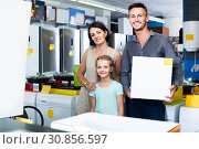 parents with daughter holding big box with new electronics in home appliance store. Стоковое фото, фотограф Яков Филимонов / Фотобанк Лори