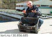 Купить «Man demonstrating freshly caught fish», фото № 30856685, снято 19 марта 2019 г. (c) Яков Филимонов / Фотобанк Лори