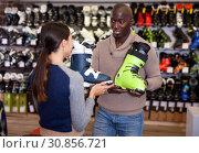 Купить «Young African American man with his girlfriend choosing new ski boots in ski equipment shop», фото № 30856721, снято 16 апреля 2019 г. (c) Яков Филимонов / Фотобанк Лори
