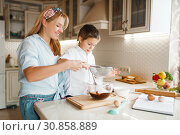 Купить «Mother with son mixing melted chocolate in a bowl», фото № 30858889, снято 6 марта 2019 г. (c) Tryapitsyn Sergiy / Фотобанк Лори