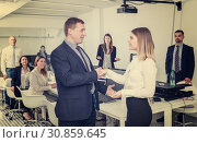 Купить «businessman and businesswoman shaking hands in office», фото № 30859645, снято 21 апреля 2018 г. (c) Яков Филимонов / Фотобанк Лори