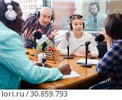 Купить «Multinational group of cheerful young adults emotionally discussing in radio studio», фото № 30859793, снято 16 марта 2019 г. (c) Яков Филимонов / Фотобанк Лори