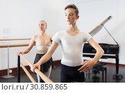 Купить «Choreographer woman and young man do exercises at ballet bar in hall with mirror», фото № 30859865, снято 26 апреля 2019 г. (c) Яков Филимонов / Фотобанк Лори