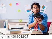 Купить «Young male financial manager working in the office», фото № 30864905, снято 11 октября 2018 г. (c) Elnur / Фотобанк Лори