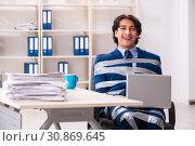 Купить «Young tied male employee in the office», фото № 30869645, снято 18 декабря 2018 г. (c) Elnur / Фотобанк Лори