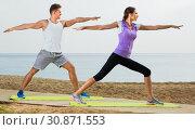 Купить «Couple do exercises on beach by ocean at daytime», фото № 30871553, снято 26 июня 2019 г. (c) Яков Филимонов / Фотобанк Лори