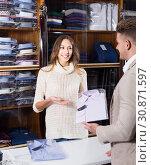 Female shopping assistant offering various shirts in men's cloths store. Стоковое фото, фотограф Яков Филимонов / Фотобанк Лори