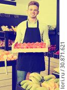 Купить «Male seller in grocery shop», фото № 30871621, снято 23 ноября 2016 г. (c) Яков Филимонов / Фотобанк Лори