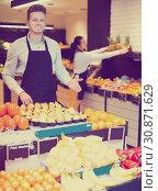 Купить «Shopping assistant demonstrating assortment», фото № 30871629, снято 23 ноября 2016 г. (c) Яков Филимонов / Фотобанк Лори