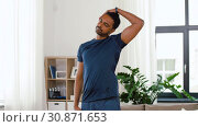 Купить «man with fitness tracker stretching body at home», видеоролик № 30871653, снято 27 мая 2019 г. (c) Syda Productions / Фотобанк Лори