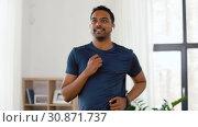 Купить «man with wireless earphones exercising at home», видеоролик № 30871737, снято 27 мая 2019 г. (c) Syda Productions / Фотобанк Лори