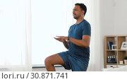 Купить «indian man jumping on spot at home», видеоролик № 30871741, снято 27 мая 2019 г. (c) Syda Productions / Фотобанк Лори