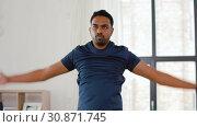 Купить «indian man doing jumping jack exercise at home», видеоролик № 30871745, снято 27 мая 2019 г. (c) Syda Productions / Фотобанк Лори