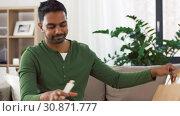 Купить «smiling indian man unpacking takeaway food at home», видеоролик № 30871777, снято 27 мая 2019 г. (c) Syda Productions / Фотобанк Лори