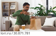 indian man with takeaway coffee and food at home. Стоковое видео, видеограф Syda Productions / Фотобанк Лори