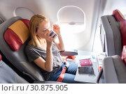 Купить «Woman drinking coffee on commercial passengers airplane during flight.», фото № 30875905, снято 3 апреля 2020 г. (c) Matej Kastelic / Фотобанк Лори