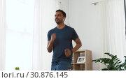 Купить «man with wireless earphones exercising at home», видеоролик № 30876145, снято 27 мая 2019 г. (c) Syda Productions / Фотобанк Лори