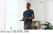 Купить «indian man jumping on spot at home», видеоролик № 30876149, снято 27 мая 2019 г. (c) Syda Productions / Фотобанк Лори