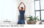 Купить «indian man doing jumping jack exercise at home», видеоролик № 30876153, снято 27 мая 2019 г. (c) Syda Productions / Фотобанк Лори