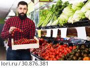 Купить «Assistant demonstrating tomatoes», фото № 30876381, снято 15 ноября 2016 г. (c) Яков Филимонов / Фотобанк Лори
