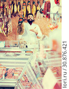 Купить «Positive man seller showing jamon», фото № 30876421, снято 16 ноября 2016 г. (c) Яков Филимонов / Фотобанк Лори