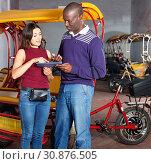 Polite African-American bikecab driver talking to young woman, offering rickshaw service. Стоковое фото, фотограф Яков Филимонов / Фотобанк Лори