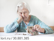 Concerned elderly woman sitting at the table counting money in her wallet. Стоковое фото, фотограф Matej Kastelic / Фотобанк Лори
