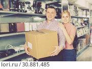 Купить «Positive young family with box of purchases in modern shop», фото № 30881485, снято 1 марта 2018 г. (c) Яков Филимонов / Фотобанк Лори