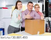 Купить «Positive family of three holding thumbs up in store with packed household appliances», фото № 30881493, снято 1 марта 2018 г. (c) Яков Филимонов / Фотобанк Лори