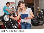 Купить «female reads a description of a motobike», фото № 30881833, снято 8 мая 2018 г. (c) Яков Филимонов / Фотобанк Лори