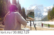 Dolomites. A young woman sitting on the coast of the river and drawing a painting using easel. Стоковое видео, видеограф Константин Шишкин / Фотобанк Лори