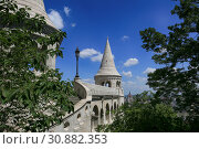 Купить «View through the leaves of trees to the towers in the Fisherman's Bastion and the Parliament building in Budapest, Hungary», фото № 30882353, снято 3 июня 2019 г. (c) Яна Королёва / Фотобанк Лори